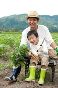 畑の中で一輪車に腰掛ける父と男の子の写真素材 [FYI01531318]