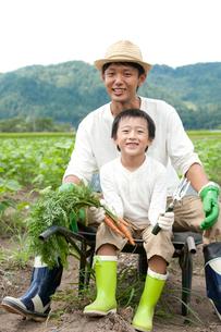畑の中で一輪車に腰掛ける父と男の子の写真素材 [FYI01531375]