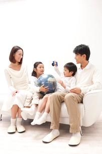 地球儀と人工衛星模型で遊ぶ子供の四人家族の写真素材 [FYI01531433]