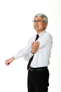 痛む腕に手をやる中年男性の写真素材 [FYI01531483]