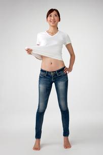 お腹を出したTシャツとジーンズを着た20代女性の写真素材 [FYI01531525]