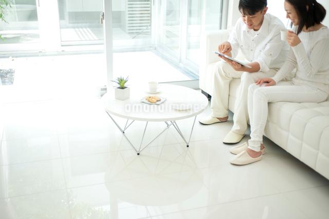 白いソファのリビングでタブレットPCをするカップルの写真素材 [FYI01531563]