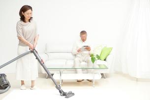 掃除機をかける中高年女性とソファの男性夫婦の写真素材 [FYI01531615]