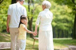 公園を孫と散歩するシニア夫婦の写真素材 [FYI01531635]