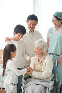 車椅子の老人夫婦と孫と介護ヘルパーの写真素材 [FYI01531641]