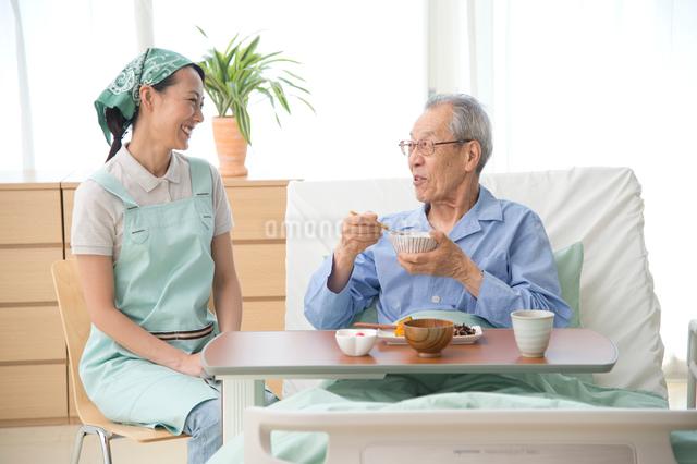 介護ベッドの老人に食事をさせる介護ヘルパーの写真素材 [FYI01531649]