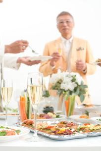 シャンパンと料理を楽しむホームパーティーの人達の写真素材 [FYI01531741]