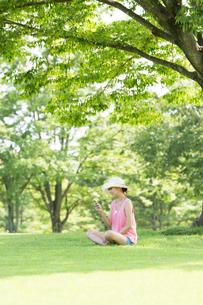 携帯電話を見る白い帽子の女性の写真素材 [FYI01531827]