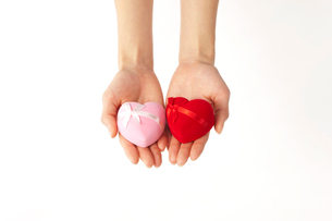 ピンクと赤のジュエリーボックスを乗せた両手の写真素材 [FYI01531841]