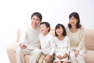 ソファに座ってTVを見ている四人家族の写真素材 [FYI01532015]