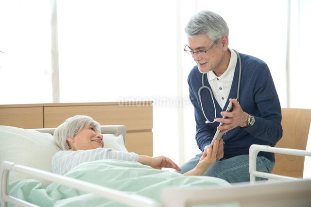 介護ベッドの老人を診察する医者の写真素材 [FYI01532105]