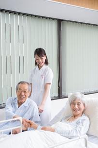 ベッドと車椅子の入院シニア患者と看護師の写真素材 [FYI01532383]