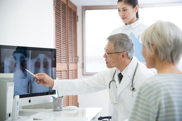 レントゲン写真を見る医者と看護師とシニア女性患者の写真素材 [FYI01532411]