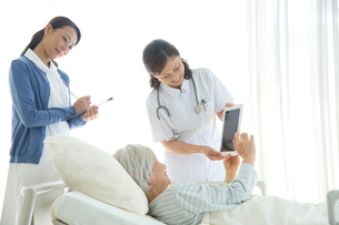 病院ベッドの老人を診察する女医と看護師の写真素材 [FYI01532415]