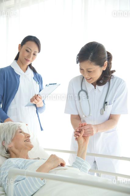 病院ベッドの老人の手を握る女医と看護師の写真素材 [FYI01532513]