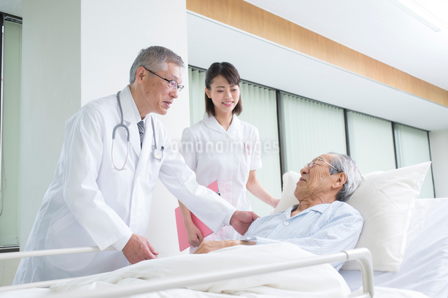 ベッドの入院シニア患者を診察する医者と看護師の写真素材 [FYI01532522]
