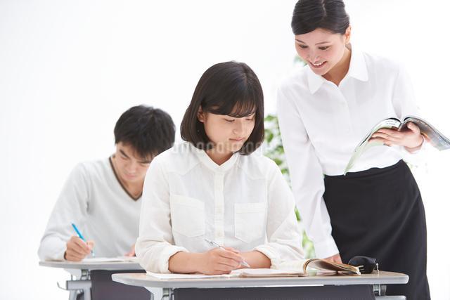 塾で授業中の高校生男女と女性教師の写真素材 [FYI01532583]