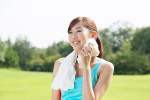 タオルで汗を拭くスポーツウェアの女性の写真素材 [FYI01532601]