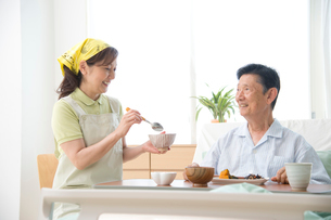 介護ベッドの老人に食事をさせる介護ヘルパーの写真素材 [FYI01532672]