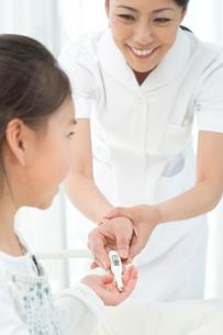 患者の女の子に体温計を渡す看護師の写真素材 [FYI01532867]