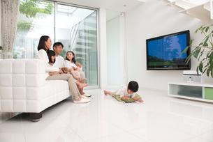 リビングでテレビをみる家族と犬の写真素材 [FYI01532909]