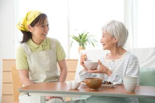 介護ベッドの老人に食事をさせる介護ヘルパーの写真素材 [FYI01532942]