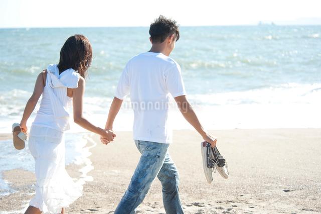 海辺で裸足で戯れるカップルの写真素材 [FYI01533065]