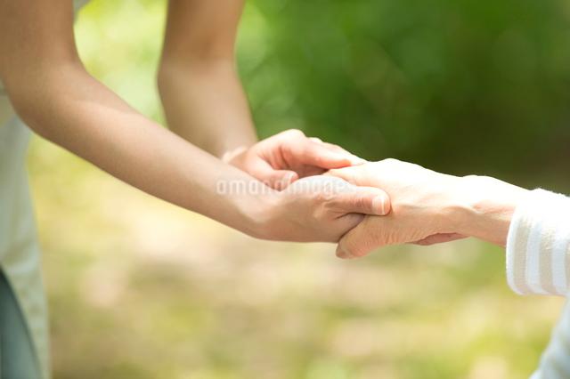 車椅子の老人と介護ヘルパーの手の写真素材 [FYI01533251]
