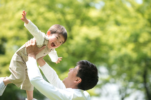 公園で男の子を抱き上げる父の写真素材 [FYI01533365]