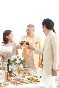 赤ワインで乾杯する中高年夫婦とホームパーティーのお客様の写真素材 [FYI01533382]