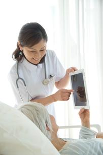 病院ベッドの老人を診察する女医の写真素材 [FYI01533644]