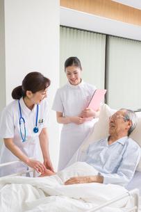 ベッドの入院シニア患者を診察する女医と看護師の写真素材 [FYI01533694]