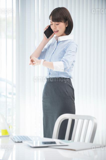 立って携帯電話してウェアラブルウォッチを見るOLの写真素材 [FYI01533989]