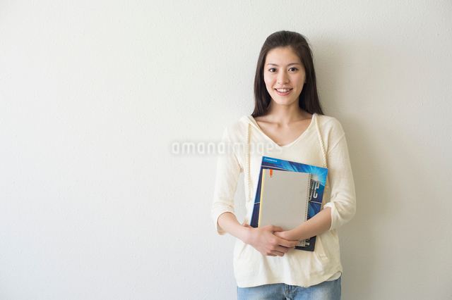 教科書を持って立つ女子大生の写真素材 [FYI01534061]