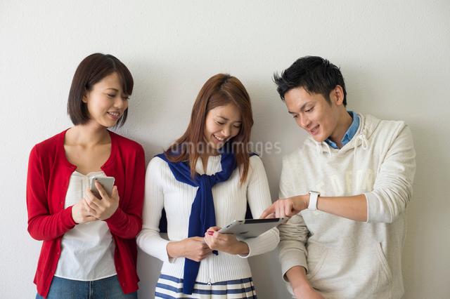 ウェアラブルウォッチとPCとスマホの大学生男女三人の写真素材 [FYI01534129]