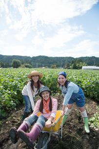 畑で一輪車で遊ぶ女性三人の写真素材 [FYI01534355]