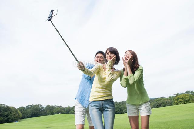 自撮棒で写真を撮る公園の若者三人の写真素材 [FYI01534387]
