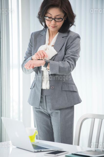 立ってウェアラブルウォッチを見るビジネスウーマンの写真素材 [FYI01534537]