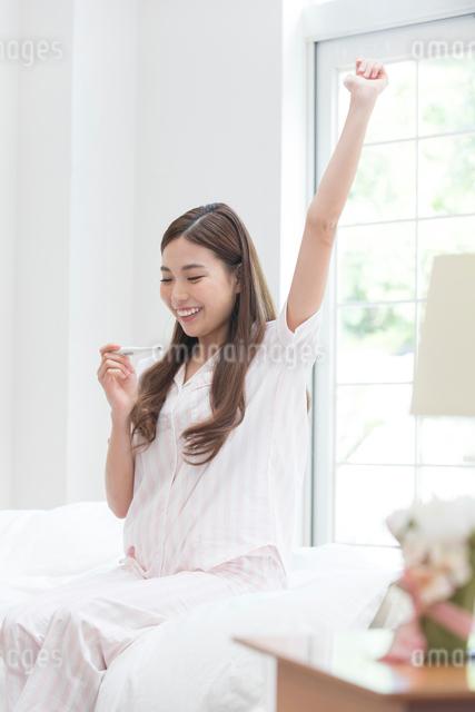 ベッドで体温計を見るパジャマの女性の写真素材 [FYI01534675]