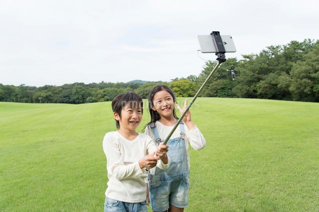 自撮棒で写真を撮る公園の子供男女の写真素材 [FYI01534682]