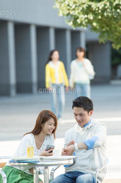 カフェテリアでウェラブルウォッチを見る大学生カップルの写真素材 [FYI01534768]