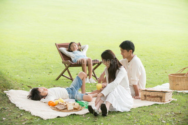 ピクニックに来た公園で寛ぐ四人家族の写真素材 [FYI01534777]
