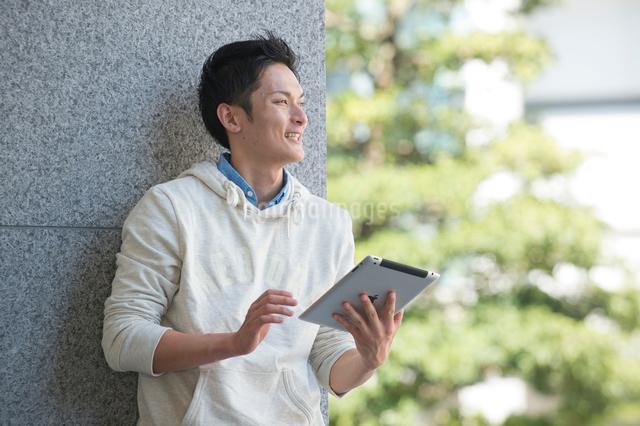 キャンパスでタブレットPCをする大学生男子の写真素材 [FYI01534911]