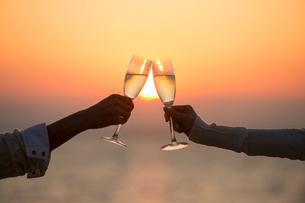 夕日の海岸でシャンパンで乾杯するカップルの手元の写真素材 [FYI01534914]