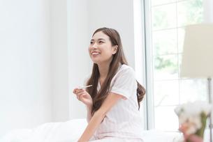 ベッドで体温計を見るパジャマの女性の写真素材 [FYI01534929]