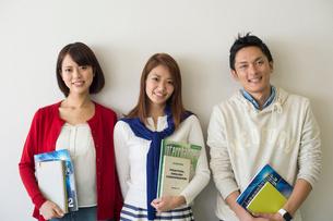 教科書を持って立つ大学生男女三人の写真素材 [FYI01535160]