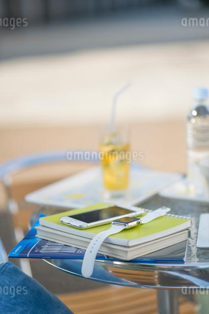 テーブルに置かれた教科書とウェアラブルウォッチとスマホの写真素材 [FYI01535223]