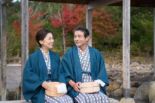 秋の温泉旅館で浴衣の桶と手拭を持つ中高年夫婦の写真素材 [FYI01535377]