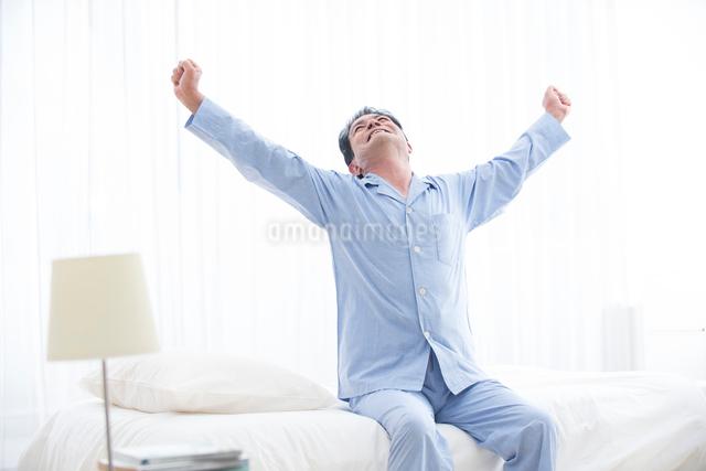 起床し背伸びするパジャマの中高年男性の写真素材 [FYI01535423]