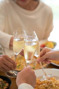 シャンパンで乾杯をする仲間の手元と料理の写真素材 [FYI01535463]